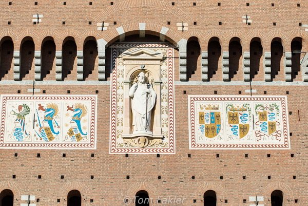 A statue of St. Ambrose, patron saint of Milan, decorates the Filarete Tower of Sforza Castle, flanked by the Visconti and Sforza coat of arms, a snake/dragon swallowing a person and black imperial eagle.