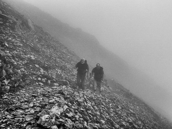 Two hikers coming out of the fog that engulfed the Swiss Alps