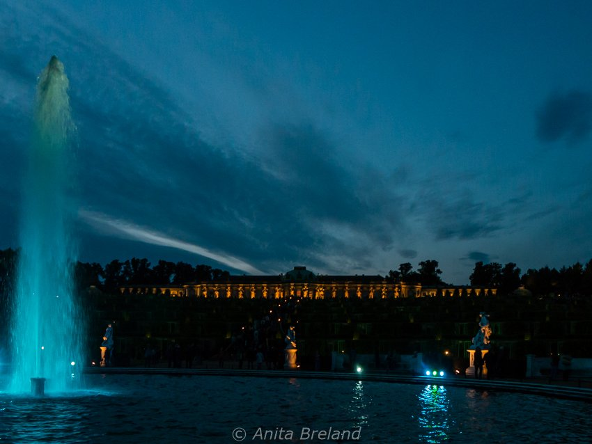 Schloss Sanssouci glows as darkness falls, and the park's paths and fountains are lit by small electric torches.