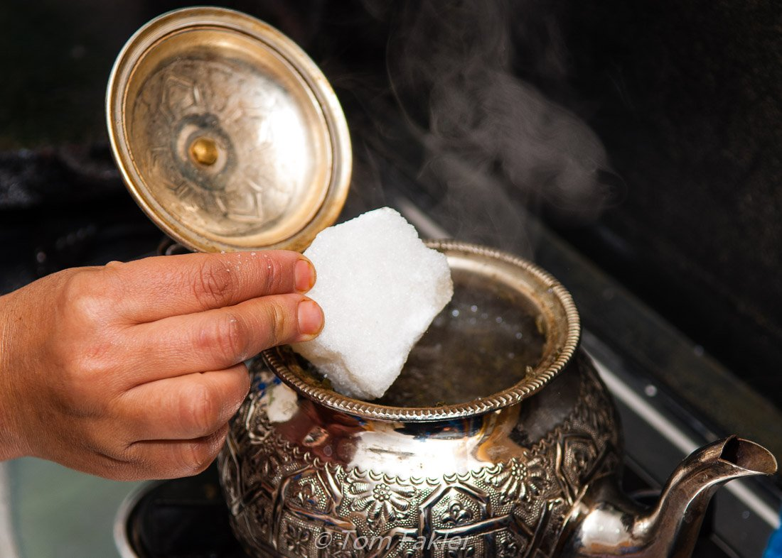 Adding sugar to Moroccan mint tea