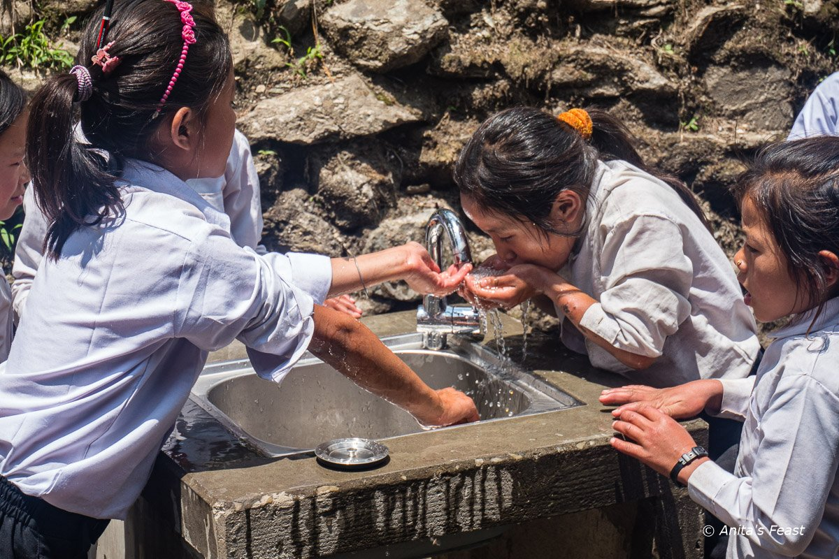Girls drinking from a fountain