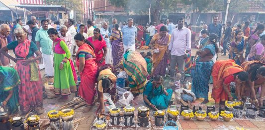 Women cooking pongal over small fires