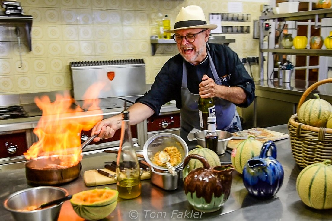 Chef laughing as he flames a dish in the kitchen