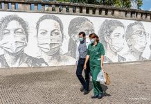 Masked health workers in front of mural honoring pandemic responders