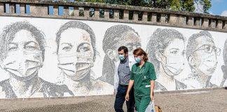 Masked health workers in front of mural honoring pandemic responders
