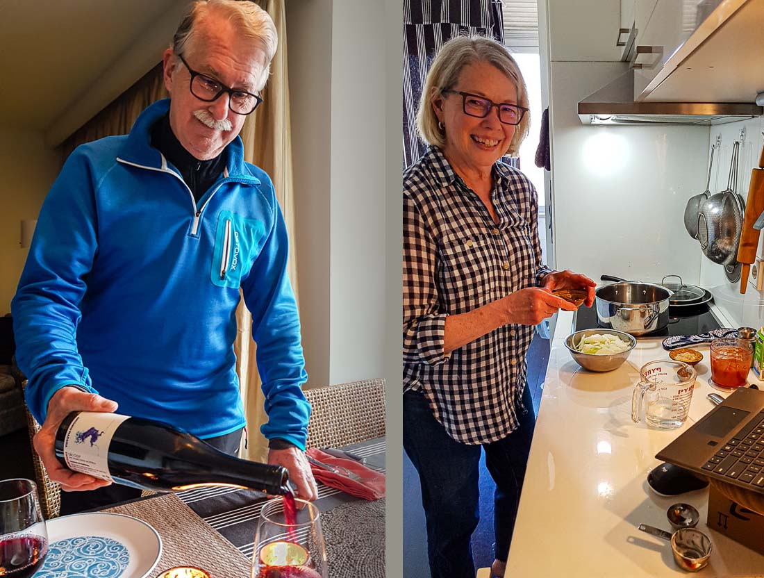 Man pouring wine, woman smiling in her kitchen as she cooks